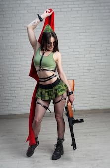 Kobieta z czerwoną flagą w mundurze wojskowym zsrr z pistoletem asg ppsz-41