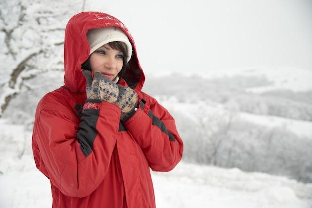 Kobieta z czerwoną kurtką i rękawiczkami w lesie śniegu