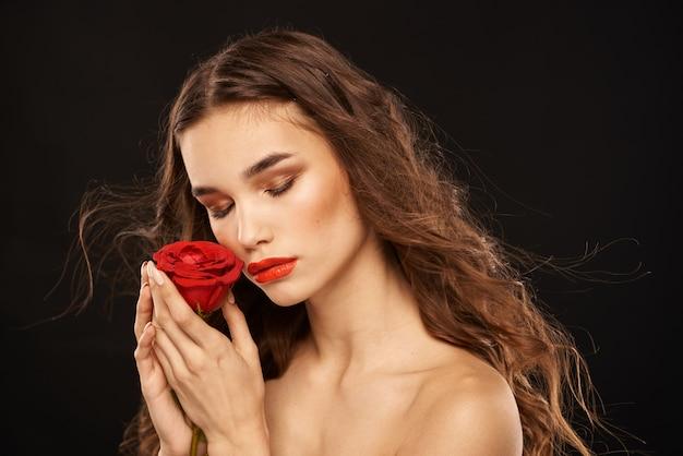 Kobieta z czerwoną różą na ciemnych długich włosach makijaż czerwone usta.