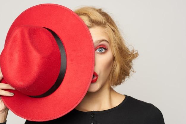 Kobieta z czerwonym kapeluszem w ręku z bliska