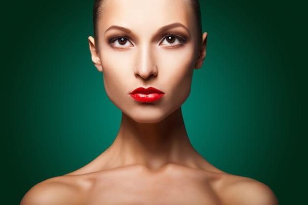 Kobieta z czerwonym makijażem i manicure na zielono