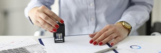 Kobieta z czerwonym manicure stawia pieczęć na dokumentach w biurze podpisywania koncepcji umowy