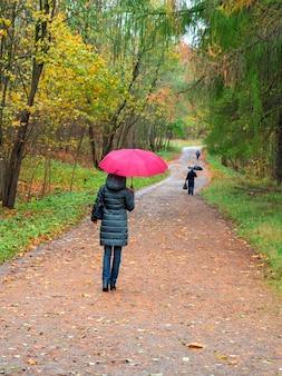 Kobieta z czerwonym parasolem idzie krętą ścieżką w deszczu.