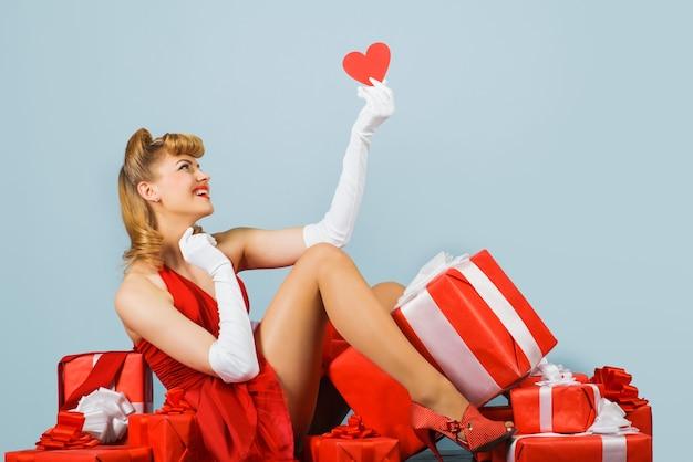 Kobieta z czerwonym sercem. walentynki. szczęśliwa dziewczyna z prezentami. wakacje. upiąć kobietę z prezentem.