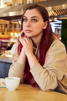 Kobieta z czerwonymi długimi włosami siedzi w kawiarni przy filiżance herbaty