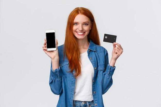 Kobieta z czerwonymi długimi włosami trzyma kartę kredytową i pokazuje smartphone