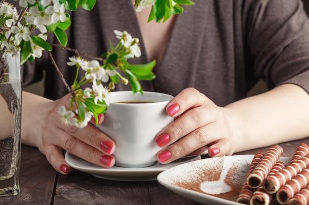 Kobieta z czerwonymi gwoździami siedzi gorącą filiżankę kawy i trzyma