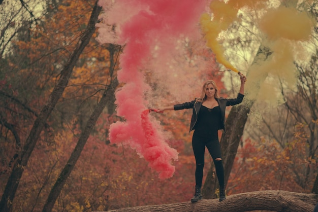 Kobieta z czerwonymi i żółtymi dymnymi bombami w jesieni