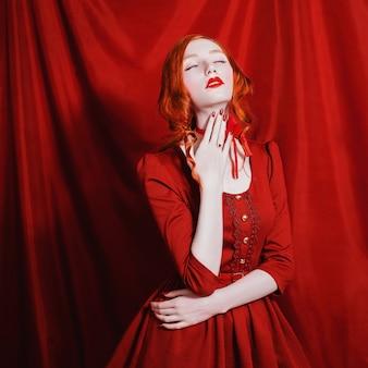 Kobieta z czerwonymi kręconymi włosami w czerwonej sukience i retro makijaż na czerwonym tle. rudowłosa dziewczyna o bladej skórze, niebieskich oczach, jasnym, niezwykłym wyglądzie, czerwonych ustach i czerwonej wstążce na szyi. czerwona magia