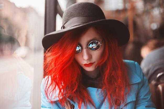 Kobieta z czerwonymi kręconymi włosami w niebieskim płaszczu i czarnymi okrągłymi okularami, jazda autobusem.