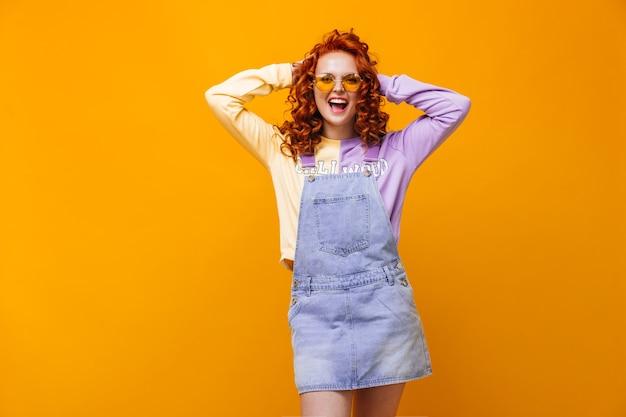 Kobieta z czerwonymi lokami mierzwi włosy