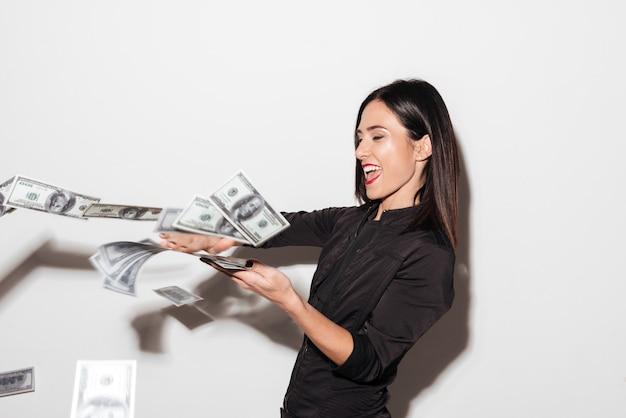 Kobieta z czerwonymi ustami rozprasza pieniądze.