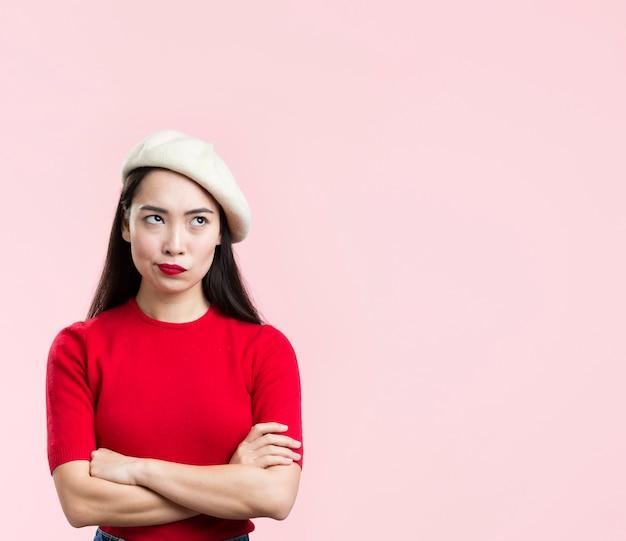 Kobieta z czerwonymi wargami stoi z rękami krzyżować