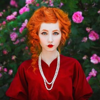Kobieta z czerwonymi włosami i czerwoną suknią slinky pozowanie na tle czerwonych róż. rudowłosa dziewczyna o bladej skórze i niebieskich oczach o jasnym, niezwykłym wyglądzie z naszyjnikiem z koralików na szyi