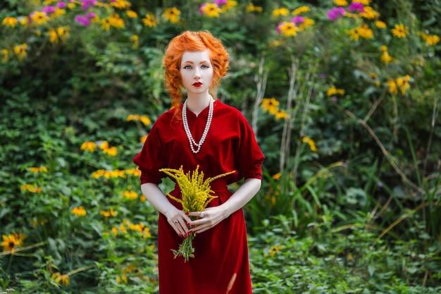 Kobieta z czerwonymi włosami i czerwoną suknią slinky z bukietem żółtych kwiatów w ręku.
