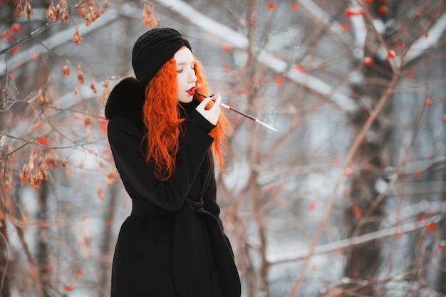 Kobieta z czerwonymi włosami w czarnym płaszczu w zimowym lesie z ustnikiem w dłoni. rudowłosa dziewczyna o jasnym wyglądzie z turbanem na głowie z papierosem. estetyka palenia