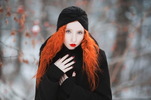 Kobieta z czerwonymi włosami w czarnym płaszczu z futrem na tle zimowego lasu. rudowłosa dziewczyna o bladej skórze i niebieskich oczach o jasnym, niezwykłym wyglądzie z turbanem na głowie. styl damski