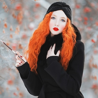 Kobieta z czerwonymi włosami w czarnym płaszczu zimowego lasu z ustnikiem w dłoni. rudowłosa dziewczyna o jasnym wyglądzie z turbanem na głowie z papierosem. estetyka palenia