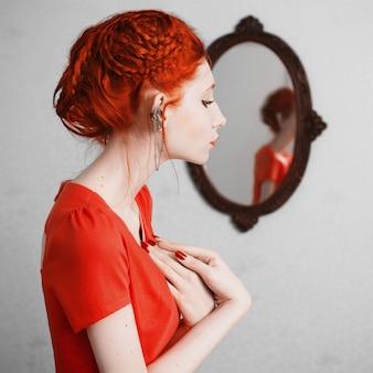 Kobieta z czerwonymi włosami w pomarańczowej sukience. rudowłosa dziewczyna o bladej skórze, jasnym niecodziennym wyglądzie, czerwonych ustach i kolczykach na uchu