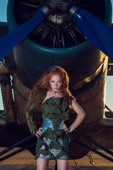 Kobieta z czerwonymi włosami w wojskowych ubraniach w pobliżu samolotu