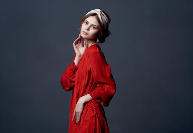 Kobieta z dekoracją z pałąkiem na głowę czerwona sukienka luksusowe ciemne tło