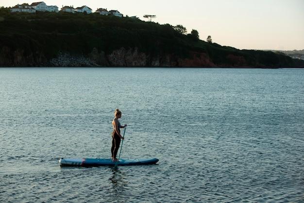Kobieta z długiego strzału na paddleboardingu