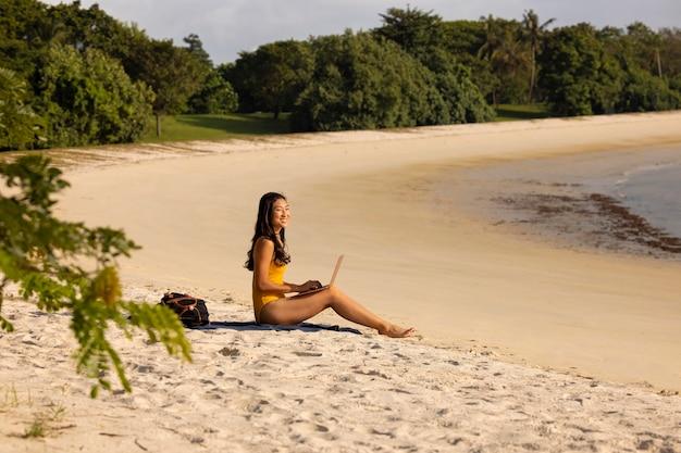 Kobieta z długiego strzału pracująca na plaży?