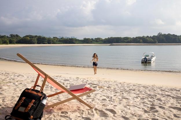 Kobieta z długiego strzału spacerująca po plaży