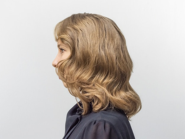Kobieta z długimi blond włosami i elegancką fryzurą w stylu retro falowane włosy w salonie piękności. widok z boku.