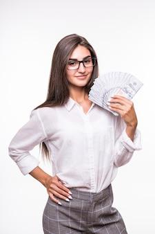 Kobieta z długimi brązowymi włosami w zwykłym ubraniu trzyma mnóstwo banknotów dolarowych na białym tle