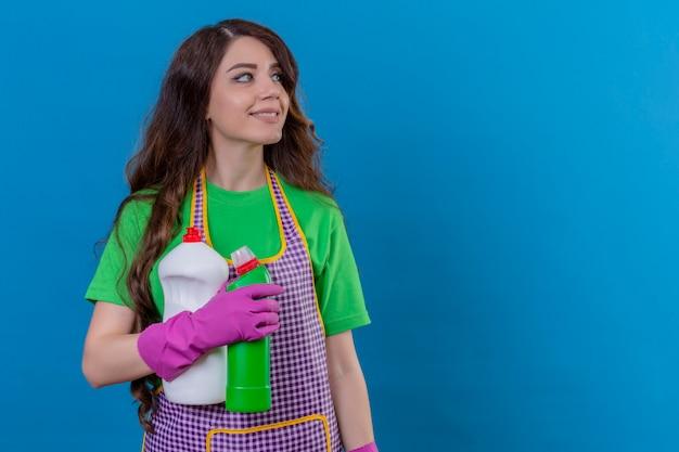 Kobieta z długimi falującymi włosami, ubrana w fartuch i gumowe rękawiczki, trzymająca butelki ze środkami czyszczącymi, patrząc na bok uśmiechnięty przyjazny stojący na niebiesko