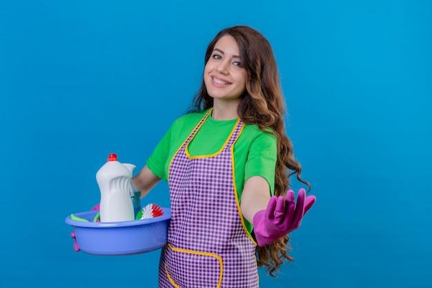 Kobieta z długimi falującymi włosami w fartuchu i gumowych rękawiczkach trzyma umywalkę pełną narzędzi czyszczących, czyniąc gest powitalny uśmiechnięty przyjazny stojąc na niebiesko