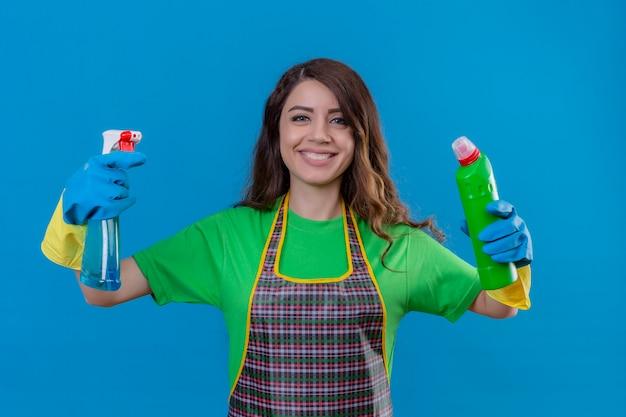 Kobieta z długimi falującymi włosami w fartuchu i gumowych rękawiczkach, trzymając butelki środków czystości w uniesionych dłoniach, uśmiechając się wesoło stojąc na niebiesko
