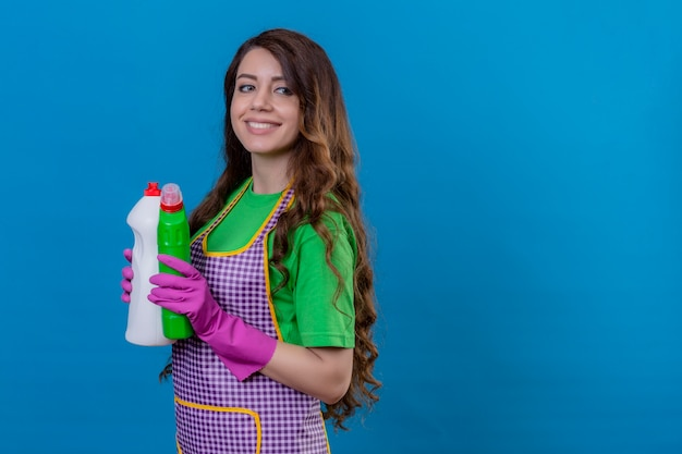 Kobieta z długimi falującymi włosami w fartuchu i gumowych rękawiczkach trzymająca butelki ze środkami czystości uśmiechnięta pewnie stojąca na niebiesko
