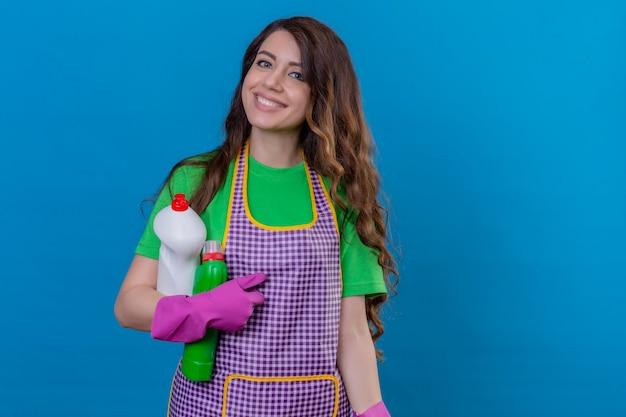 Kobieta z długimi falującymi włosami w fartuchu i gumowych rękawiczkach trzymająca butelki ze środkami czyszczącymi uśmiechnięta przyjazna pozycja na niebiesko