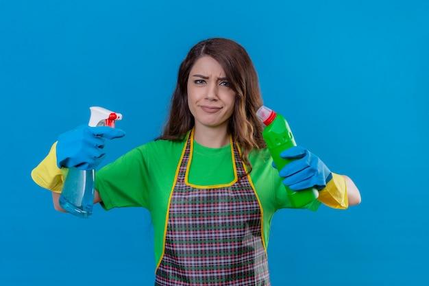 Kobieta z długimi falującymi włosami w fartuchu i gumowych rękawiczkach trzymająca butelki ze środkami czyszczącymi w uniesionych dłoniach wyglądająca niepewnie mająca wątpliwości próbująca dokonać wyboru stojąc na niebiesko