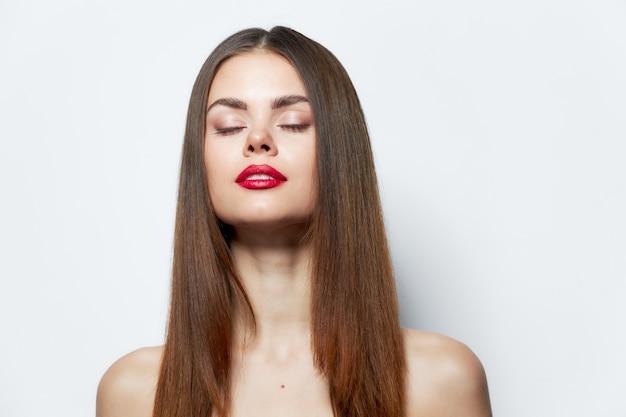 Kobieta z długimi fryzurami jasny makijaż na białym tle