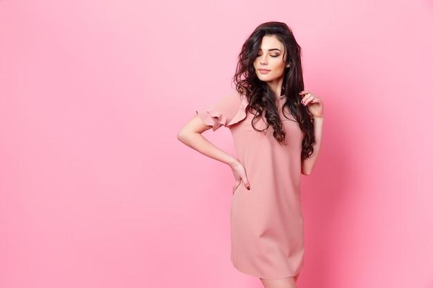 Kobieta z długimi kręconymi włosami w różowej sukience.