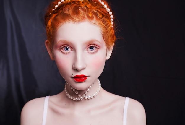 Kobieta z długimi rudymi włosami przypiętymi do głowy, naszyjnik z koralików na czarnym tle.