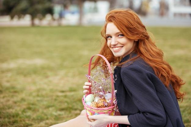 Kobieta z długimi włosami, trzymając wielkanocny kosz piknikowy