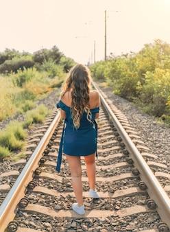 Kobieta z długimi włosami w niebieskiej sukience na widok z tyłu starych linii kolejowych