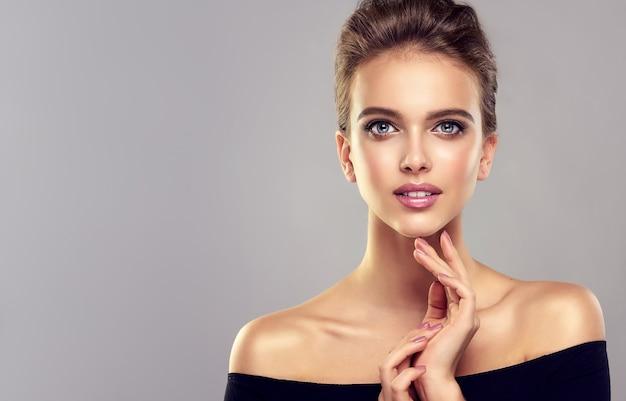 Kobieta z długimi włosami zebrana w elegancką fryzurę modelka w schludnym makijażu szczere spojrzenie na widza