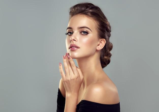 Kobieta z długimi, zadbanymi włosami zebranymi w elegancką fryzurę idealny makijaż na jej pięknej twarzy