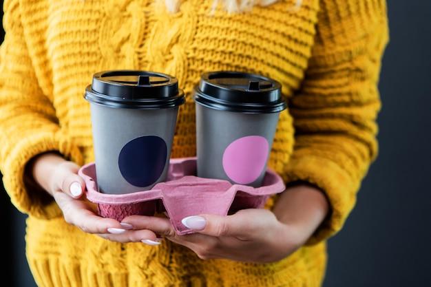 Kobieta z dobrym manicure'em trzyma w rękach specjalny pojemnik na dwie filiżanki kawy na wynos.