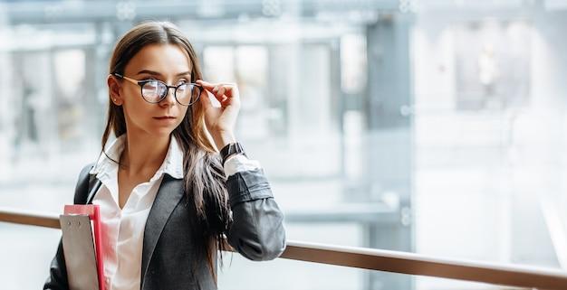 Kobieta z dokumentami do pracy. studencka dziewczyna z folderami z dokumentacją. funkcjonariusz zbierze informacje.