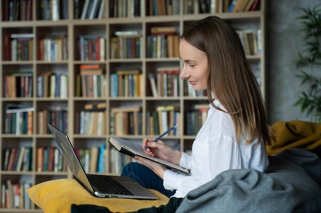 Kobieta z dokumentami za pomocą laptopa w domu przed szafą z książkami