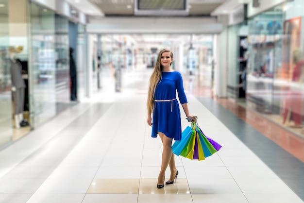 Kobieta z dolarem i torbami idzie na zakupy