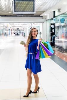 Kobieta z dolarem i torbami iść na zakupy