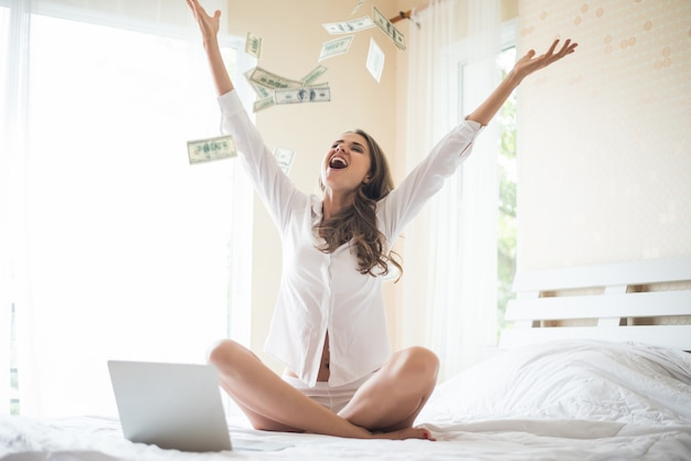 Kobieta z dolarowym banknotem na łóżku