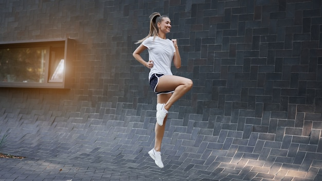 Kobieta z dopasowanym ciałem skacząca i biegająca na tle czarnej ściany
